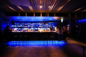 青のLED照明と、天井のディフューザー設計が印象的なバーカウンターです。